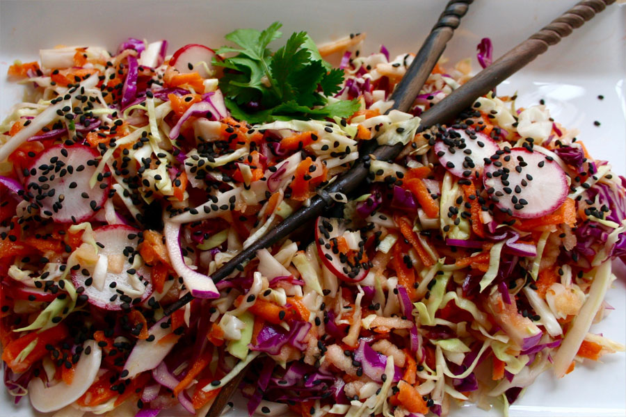 Toasted black sesame cabbage salad with chopsticks and fresh cilantro