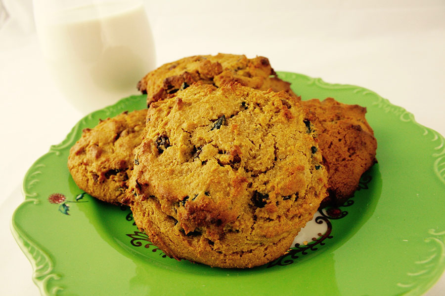 Breakfast cookies on a green dainty plate with a glass of almond milk