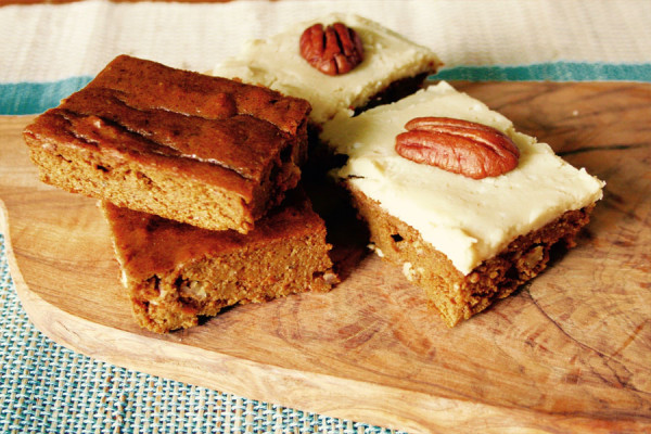 Pumpkin protein bars with maple cashew icing topped with a whole pecan