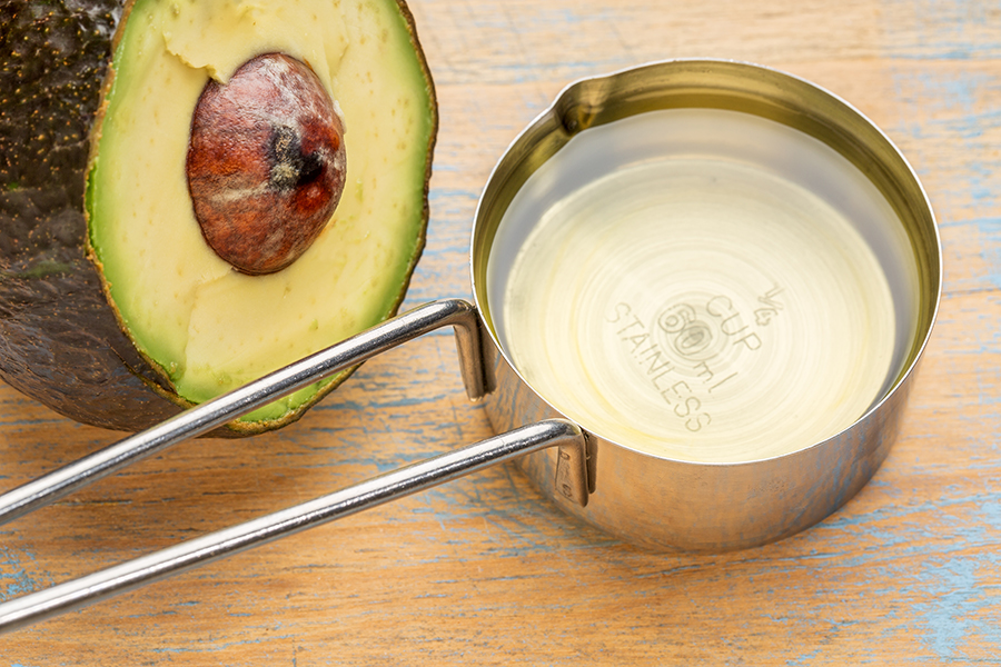 avocado oil in a metal measuring cup against painted wood with a half of avacado fruit