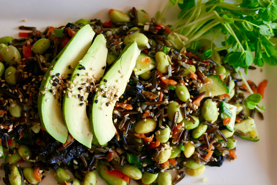 Loose sushi salad with avocado slices and fresh pea sprouts